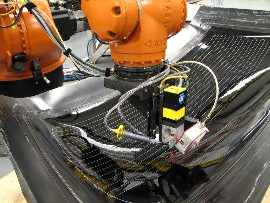 Robot Dispensing Defroster Lines from EXATEC-Designed and Built Dispensing System